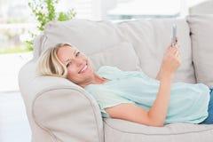 Mujer feliz que usa la tableta digital mientras que miente en el sofá Imagenes de archivo