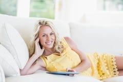 Mujer feliz que usa la tableta en el sofá Imágenes de archivo libres de regalías