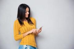 Mujer feliz que usa smartphone Fotografía de archivo