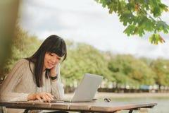 Mujer feliz que usa smartphone en la cafetería Imagenes de archivo