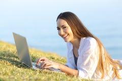 Mujer feliz que usa un ordenador portátil en la hierba que le mira Fotos de archivo