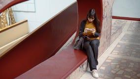 Mujer feliz que usa un smartphone dentro con las paredes de mármol