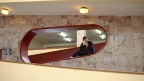 Mujer feliz que usa un smartphone dentro con las paredes de mármol metrajes