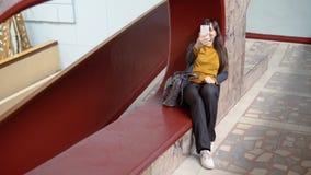 Mujer feliz que usa un smartphone dentro con las paredes de mármol almacen de metraje de vídeo