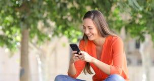 Mujer feliz que usa un teléfono elegante en un banco en un parque