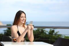 Mujer feliz que usa un teléfono elegante en una terraza de un restaurante Imagenes de archivo