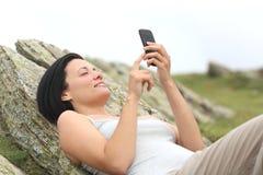 Mujer feliz que usa un teléfono móvil que miente en la montaña Foto de archivo