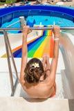Mujer feliz que va abajo de un tobogán acuático en el parque Fotografía de archivo libre de regalías