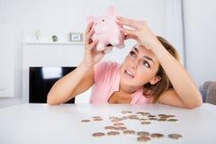 Mujer feliz que vacia sus ahorros de Piggybank Fotografía de archivo