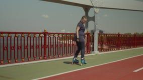 Mujer feliz rollerblading al revés en el puente del río almacen de video