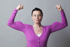Mujer feliz 40s que levanta sus músculos para arriba para la metáfora del poder femenino Foto de archivo libre de regalías