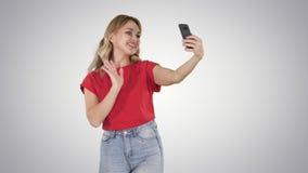 Mujer feliz 30s que lleva la camiseta roja que toma la foto del selfie mientras que camina en fondo de la pendiente metrajes