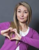 Mujer feliz 20s que muestra forma del corazón con las manos Foto de archivo libre de regalías