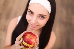 Mujer feliz sana con la manzana y cinta métrica para el concepto de la pérdida de la dieta y de peso foto de archivo