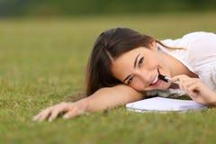 Mujer feliz sincera que miente en la escritura de la hierba Imagen de archivo