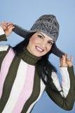 Mujer feliz sonriente con el casquillo del invierno foto de archivo