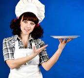 Mujer feliz sonriente del cocinero con la placa Imagen de archivo libre de regalías