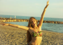 Mujer feliz sonriente delante de la playa en la puesta del sol imagen de archivo libre de regalías