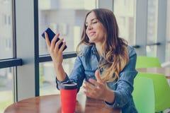 Mujer feliz sonriente emocionada que tiene un resto en un café, ella está mirando la pantalla de su SMS del teléfono móvil del te fotos de archivo libres de regalías
