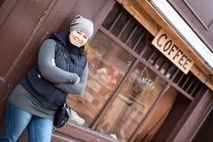 Mujer feliz sonriente que se coloca en la calle vieja de la ciudad Imagenes de archivo