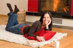 Mujer feliz viva casera que miente por la chimenea Imágenes de archivo libres de regalías