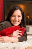 Mujer feliz viva casera que miente por la chimenea Fotos de archivo