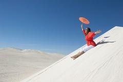 Mujer feliz y alegre que resbala abajo de la duna de arena Imágenes de archivo libres de regalías