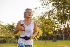 Mujer feliz y atractiva envejecida media de 40s o de 50s con el entrenamiento gris del pelo en el parque de la ciudad con los ?rb foto de archivo libre de regalías