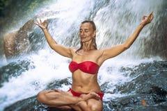 Mujer feliz y atractiva joven que hace el ejercicio de la yoga que presenta debajo de la cascada tropical hermosa que consigue la foto de archivo libre de regalías