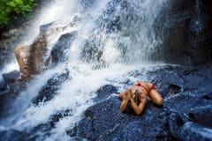 Mujer feliz y atractiva joven que hace el ejercicio de la yoga que presenta debajo de la cascada tropical hermosa que consigue la imagenes de archivo