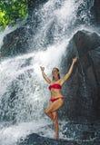Mujer feliz y atractiva joven que hace el ejercicio de la yoga que se coloca debajo de la cascada tropical hermosa que consigue l imágenes de archivo libres de regalías