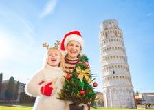Mujer feliz y bebé que sostienen el árbol de navidad Pisa, Italia Foto de archivo libre de regalías