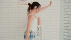 Mujer feliz y fresca que se divierte en la mañana La muchacha que lleva los pijamas baila en cocina Cámara lenta almacen de video