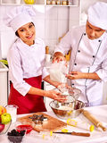Mujer feliz y hombre en sombrero del cocinero que cocinan la pasta Imagen de archivo libre de regalías