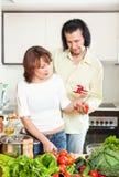 Mujer feliz y hombre que añaden las especias al pote y en el kitche casero Imágenes de archivo libres de regalías