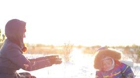 Mujer feliz y niño que juegan con nieve en el invierno almacen de metraje de vídeo