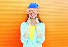 Mujer feliz y piruleta sonrientes bonitas del retrato que se divierten sobre naranja colorida Imágenes de archivo libres de regalías