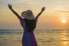 Mujer feliz y relajada joven en el sombrero del verano que mira el sol sobre el mar durante una puesta del sol hermosa asombrosa  fotografía de archivo