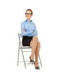 Mujer feliz y sonriente en una silla Foto de archivo