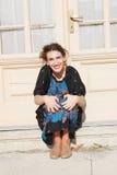 Mujer feliz y sonriente que se agacha delante de la casa Fotos de archivo