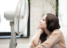 Mujer feliz y sonriente que se sienta cerca del ventilador Imagenes de archivo