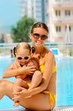 Mujer feliz y su hija cerca de la piscina Foto de archivo