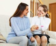 Mujer feliz y su hija con la prueba de embarazo Foto de archivo libre de regalías