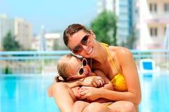 Mujer feliz y su hija en piscina Foto de archivo