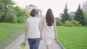 Mujer feliz y su parque que camina de la hija joven Madre adulta e hija que caminan en el parque almacen de video
