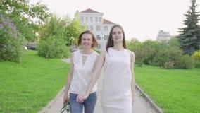 Mujer feliz y su parque que camina de la hija joven Madre adulta e hija que caminan en el parque metrajes