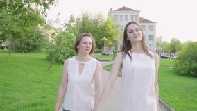 Mujer feliz y su parque que camina de la hija joven Madre adulta e hija que caminan en el parque almacen de metraje de vídeo