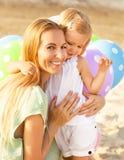 Mujer feliz y sus pequeñas hijas con impulsos al aire libre Fotografía de archivo libre de regalías