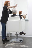 Mujer femenina del mayor de Giving Haircut To del peluquero Foto de archivo libre de regalías