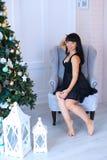 Mujer femenina encantadora que se sienta en silla y que sonríe en nea del estudio Foto de archivo